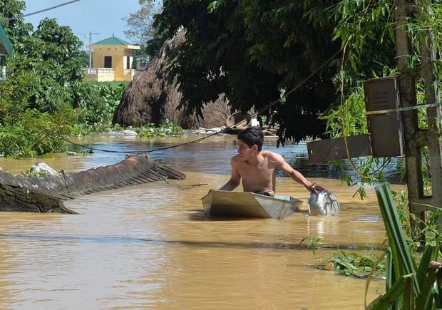 Chùm ảnh: Nhà ngập sâu đến ngang cửa, người dân Ninh Bình dùng chậu nhôm, ghế gỗ chèo thuyền đi lại trong ngõ - Ảnh 4.