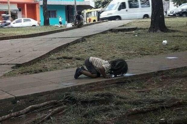 Bức ảnh em bé nghèo quỳ gối, uống vũng nước trên đường khiến cả thế giới rúng động - Ảnh 1.