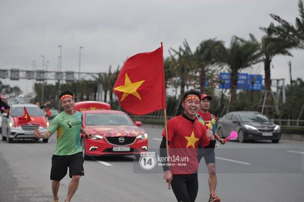 Chùm ảnh: Người hâm mộ cầm cờ Tổ quốc, chạy bộ ra sân bay Nội Bài để đón U23 Việt Nam - Ảnh 7.