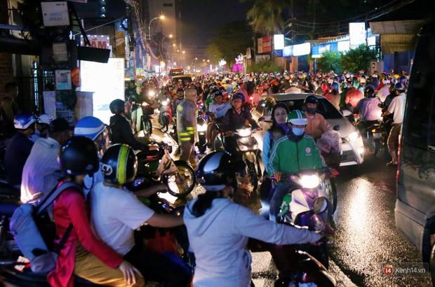 Kẹt xe kinh hoàng sau cơn mưa chiều ở Sài Gòn, trẻ em mệt mỏi ngủ trên xe máy - Ảnh 7.