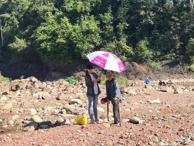 Khoảnh khắc đẹp: Hoa hậu Tiểu Vy mặc đồ giản dị, cầm ô che nắng cho người khuyết tật  - Ảnh 1.