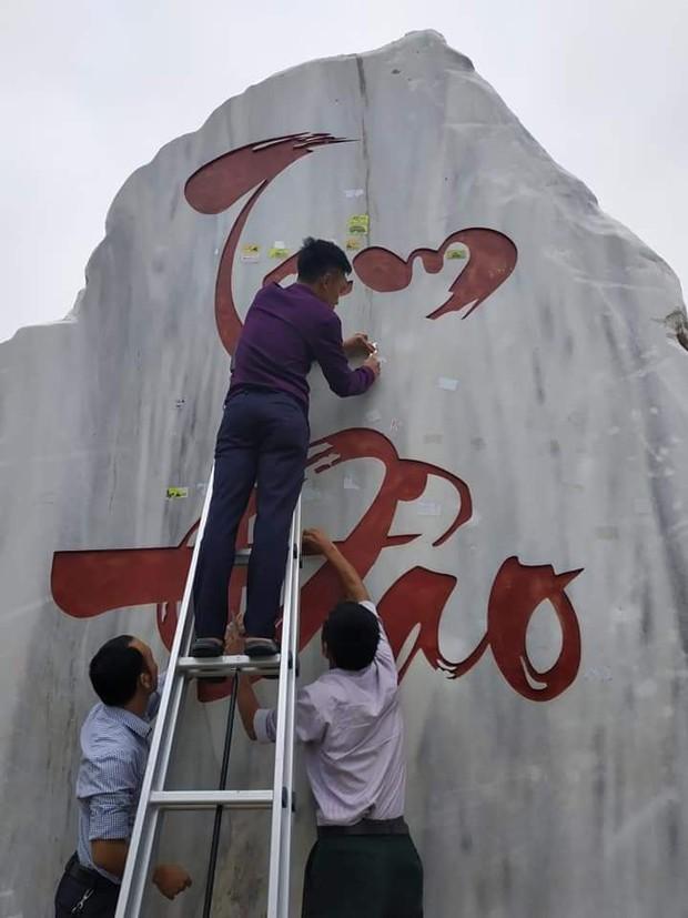 Tấm bia đá nổi tiếng Tam Đảo bị dán quá nhiều logo phượt khiến người dân phải bắc thang lên bóc - Ảnh 1.