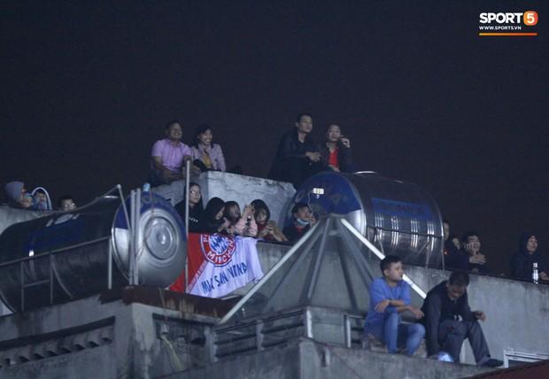 Vì đội tuyển Việt Nam, nhiều CĐV chấp nhận mạo hiểm, vắt vẻo ngồi trên nóc nhà, téc nước - Ảnh 1.