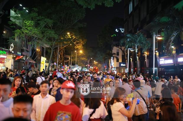 Sài Gòn tối mùng 1 Tết: Trẻ em thích thú cởi áo, nhảy vào đài phun nước đường hoa Nguyễn Huệ để nô đùa - Ảnh 1.