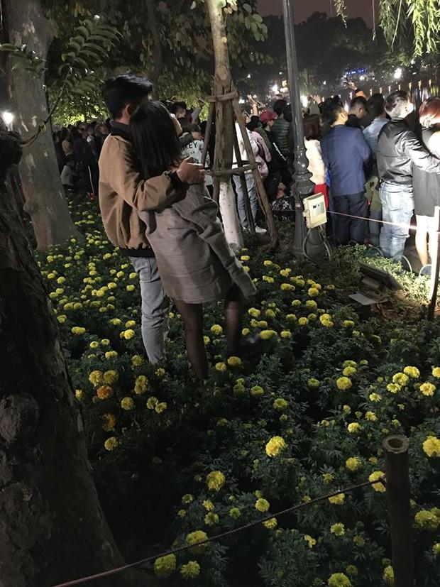 Cặp đôi vô tư nhất đêm 30 Tết: Đứng trong luống hoa xem pháo bông cho rõ - Ảnh 1.