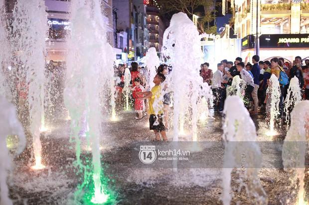 Sài Gòn tối mùng 1 Tết: Trẻ em thích thú cởi áo, nhảy vào đài phun nước đường hoa Nguyễn Huệ để nô đùa - Ảnh 11.