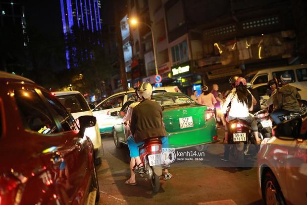 Sài Gòn tối mùng 1 Tết: Trẻ em thích thú cởi áo, nhảy vào đài phun nước đường hoa Nguyễn Huệ để nô đùa - Ảnh 4.