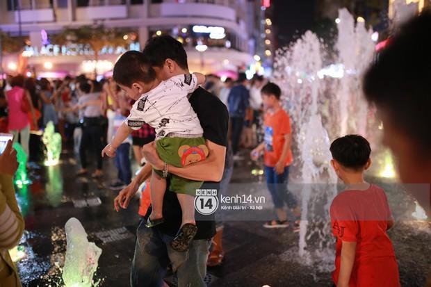 Sài Gòn tối mùng 1 Tết: Trẻ em thích thú cởi áo, nhảy vào đài phun nước đường hoa Nguyễn Huệ để nô đùa - Ảnh 12.