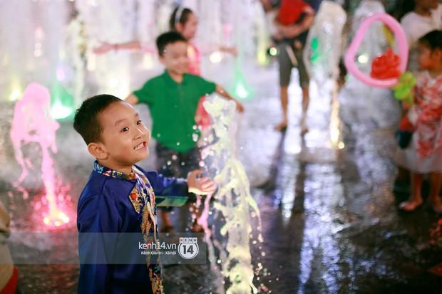 Sài Gòn tối mùng 1 Tết: Trẻ em thích thú cởi áo, nhảy vào đài phun nước đường hoa Nguyễn Huệ để nô đùa - Ảnh 10.