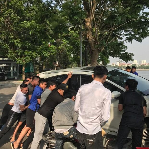 Hà Nội: Hàng chục thanh niên khiêng xe giải cứu người phụ nữ bị mắc kẹt sau cú mất lái lao lên vỉa hè - Ảnh 1.