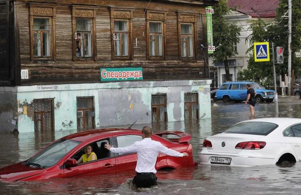 Nga: Soái ca sơ mi trắng lội nước giải cứu chị em mắc kẹt trong xe được tôn vinh như người hùng - Ảnh 1.
