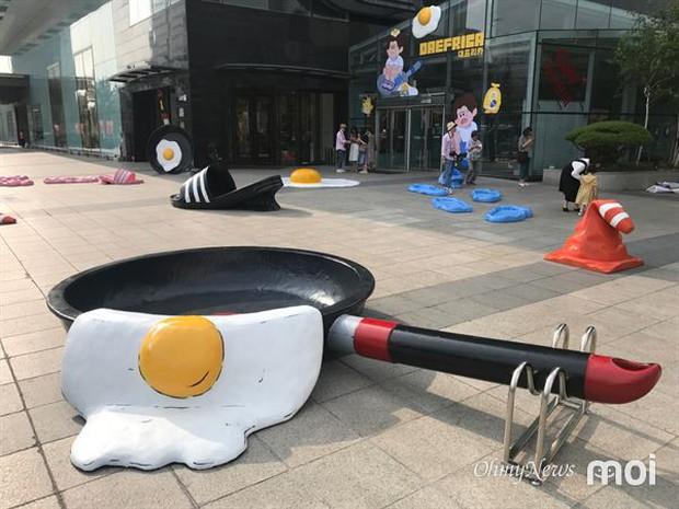 Triển lãm ngoài trời độc đáo chỉ có tại thành phố nóng nhất Hàn Quốc: Trứng rán, dép chảy nhựa đầy đường… kỷ niệm một mùa hè đáng ghét lại đến - Ảnh 2.
