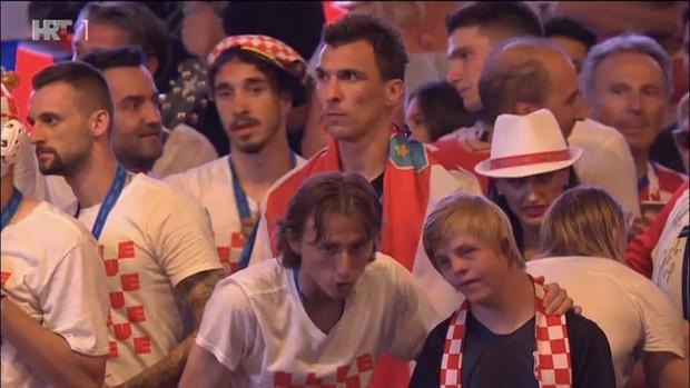 Giữa biển người hâm mộ, Luka Modric ân cần kéo tay cậu bé mắc hội chứng Down lên sân khấu ăn mừng - Ảnh 3.