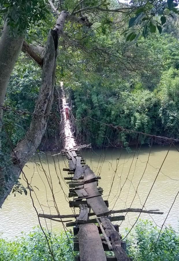 Cận cảnh người dân thấp thỏm vượt qua những cây cầu treo giữa dòng nước cuồn cuộn từ sông, suối Lâm Đồng - Ảnh 2.
