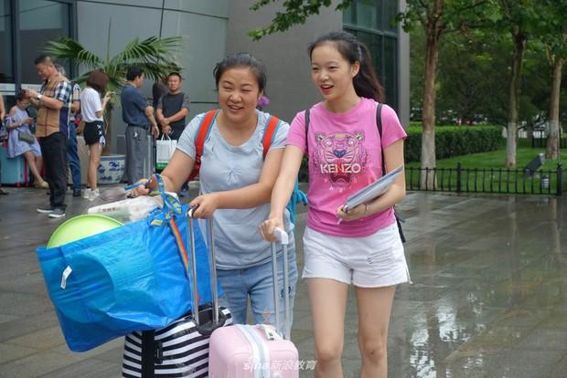 Chùm ảnh cha mẹ đội mưa, tay xách nách mang đưa con lên thành phố nhập học: Tấm lòng đấng sinh thành mấy ai hiểu - Ảnh 1.
