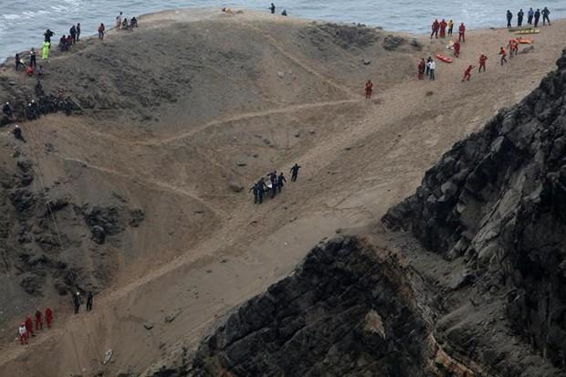 Ảnh: Gian nan cứu hộ chiếc xe bus lao xuống vực sâu cạnh biển ở Peru - Ảnh 9.