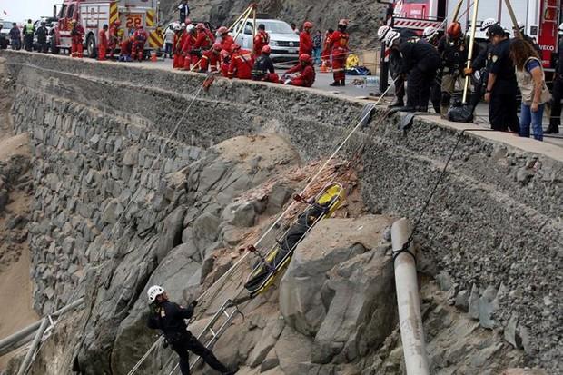 Ảnh: Gian nan cứu hộ chiếc xe bus lao xuống vực sâu cạnh biển ở Peru - Ảnh 10.