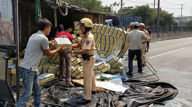 Hàng trăm thùng nước ngọt đổ ra đường, người dân Sài Gòn thu gom giúp tài xế - Ảnh 1.