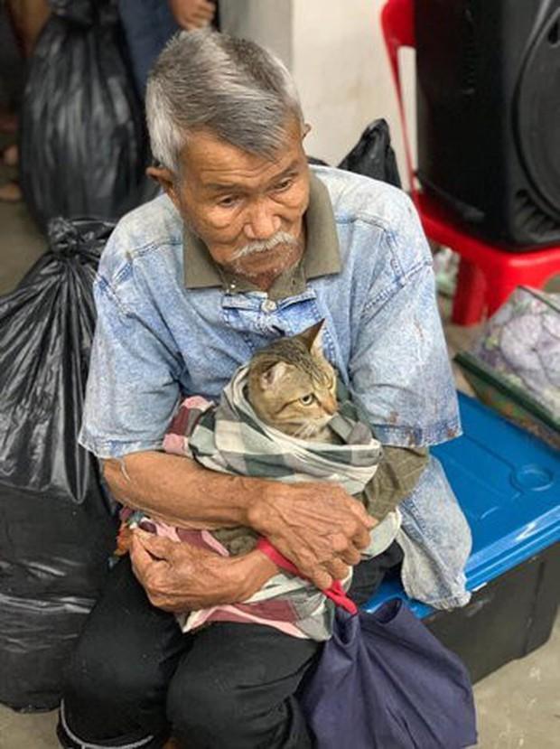 Cụ ông gây xúc động khi ôm khư khư chú mèo cưng đi tránh cơn bão lớn nhất 3 thập kỷ ở Thái Lan - Ảnh 2.
