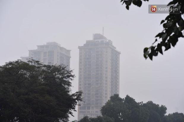 Giữa trưa Hà Nội vẫn chìm trong sương mù dày đặc, nóc các tòa cao tầng gần như biến mất hoàn toàn - Ảnh 1.