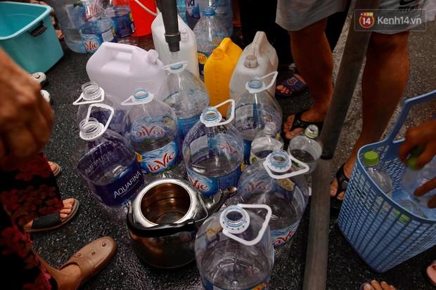 Ảnh, clip: Người dân chung cư HH Linh Đàm tiếp tục xếp hàng nhận nước sạch miễn phí, mòn mỏi chờ kết quả giám định nguồn nước có mùi lạ - Ảnh 9.