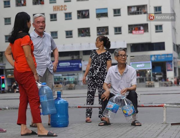 Ảnh, clip: Người dân chung cư HH Linh Đàm tiếp tục xếp hàng nhận nước sạch miễn phí, mòn mỏi chờ kết quả giám định nguồn nước có mùi lạ - Ảnh 2.