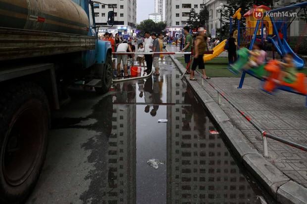 Ảnh, clip: Người dân chung cư HH Linh Đàm tiếp tục xếp hàng nhận nước sạch miễn phí, mòn mỏi chờ kết quả giám định nguồn nước có mùi lạ - Ảnh 12.