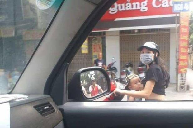 Mẹ trẻ Hà Nội vừa đi xe máy vừa thản nhiên vạch áo cho con bú khiến nhiều người nóng mắt - Ảnh 1.
