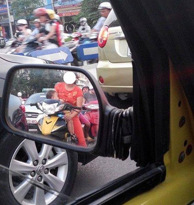 Mẹ trẻ Hà Nội vừa đi xe máy vừa thản nhiên vạch áo cho con bú khiến nhiều người nóng mắt - Ảnh 4.