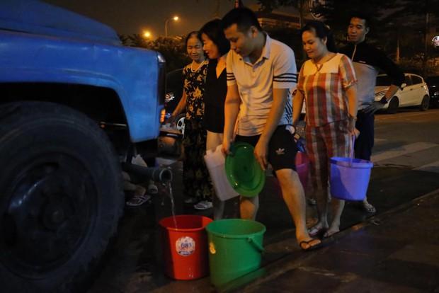 Ảnh: Người dân ở nhiều khu đô thị Hà Nội thức trắng đêm, xếp hàng chờ nhận từng xô nước sạch - Ảnh 16.