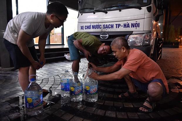Ảnh: Người dân ở nhiều khu đô thị Hà Nội thức trắng đêm, xếp hàng chờ nhận từng xô nước sạch - Ảnh 3.