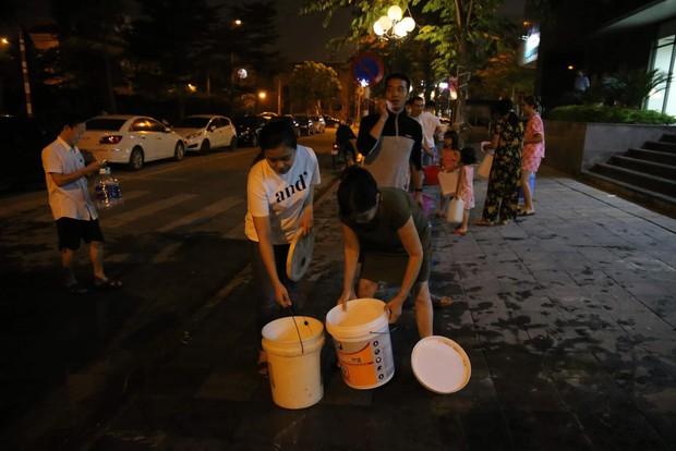 Ảnh: Người dân ở nhiều khu đô thị Hà Nội thức trắng đêm, xếp hàng chờ nhận từng xô nước sạch - Ảnh 17.