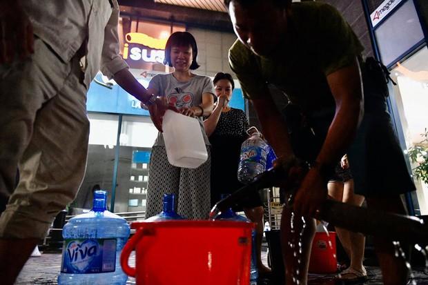 Ảnh: Người dân ở nhiều khu đô thị Hà Nội thức trắng đêm, xếp hàng chờ nhận từng xô nước sạch - Ảnh 8.