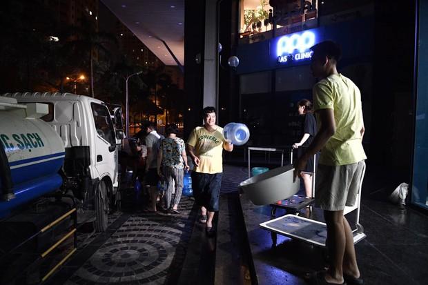 Ảnh: Người dân ở nhiều khu đô thị Hà Nội thức trắng đêm, xếp hàng chờ nhận từng xô nước sạch - Ảnh 12.