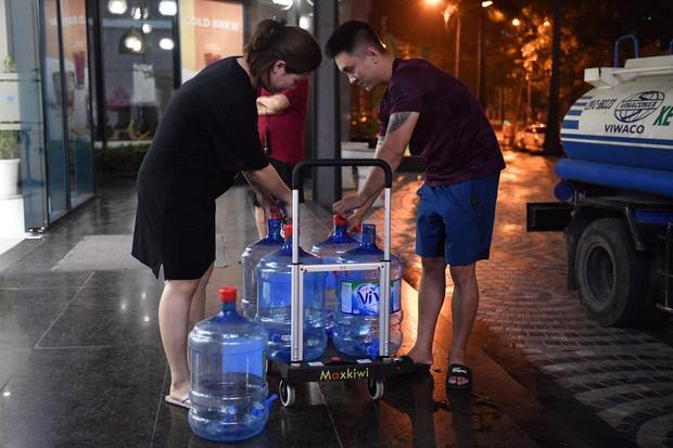 Ảnh: Người dân ở nhiều khu đô thị Hà Nội thức trắng đêm, xếp hàng chờ nhận từng xô nước sạch - Ảnh 4.