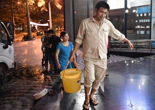 Ảnh: Người dân ở nhiều khu đô thị Hà Nội thức trắng đêm, xếp hàng chờ nhận từng xô nước sạch - Ảnh 9.