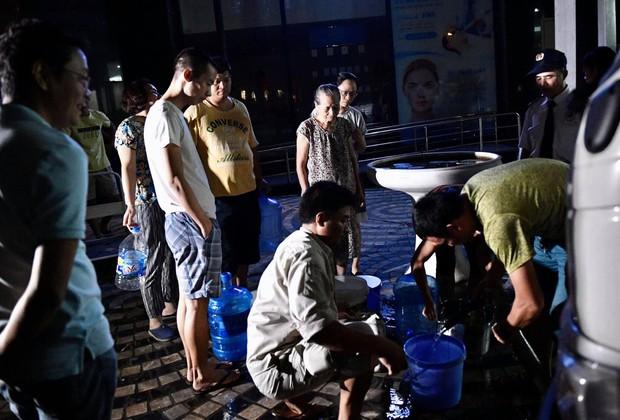 Ảnh: Người dân ở nhiều khu đô thị Hà Nội thức trắng đêm, xếp hàng chờ nhận từng xô nước sạch - Ảnh 14.