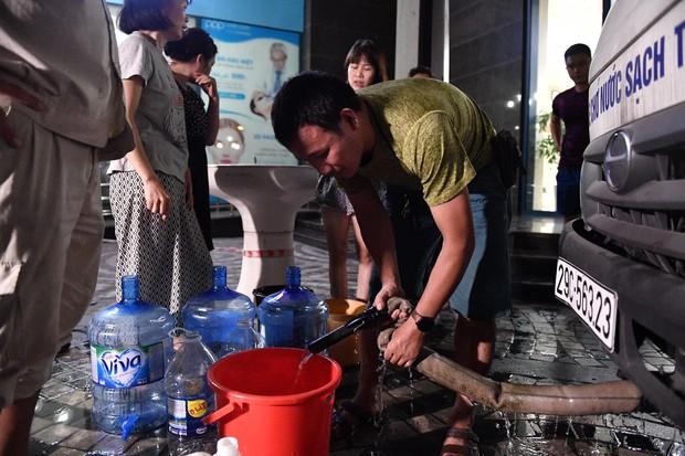 Ảnh: Người dân ở nhiều khu đô thị Hà Nội thức trắng đêm, xếp hàng chờ nhận từng xô nước sạch - Ảnh 7.