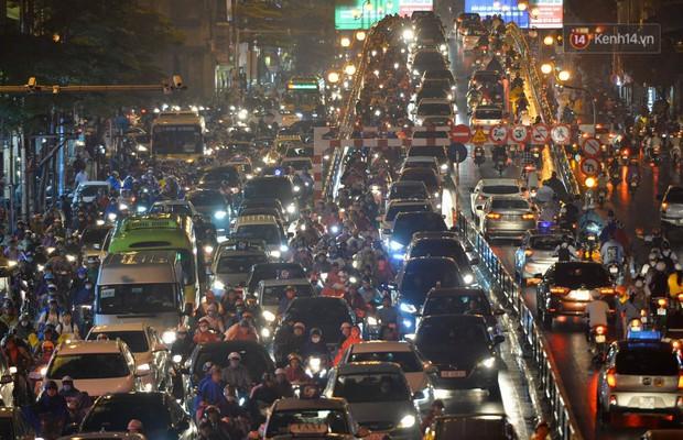 Ảnh: Mưa to đúng giờ tan tầm, nhiều tuyến đường thủ đô ùn tắc cả cây số, người dân vất vả đội mưa về nhà - Ảnh 1.