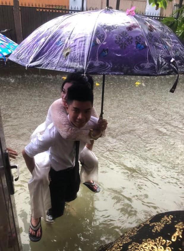 Em gái mưa phiên bản lũ lụt: Câu chuyện đằng sau bức ảnh chú rể cõng cô dâu đứng giữa biển nước đang nổi rần rần MXH - Ảnh 1.