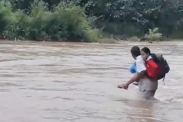 Bất chấp nguy hiểm, cha cõng con vượt qua dòng sông chảy xiết đến trường - Ảnh 1.