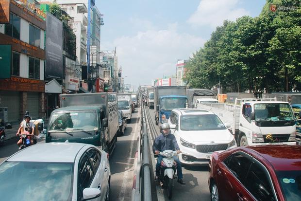 Chùm ảnh: Cửa ngõ sân bay Tân Sơn Nhất liên tục kẹt xe bất thường, ô tô dàn 2 hàng ép xe máy trên cầu vượt - Ảnh 1.
