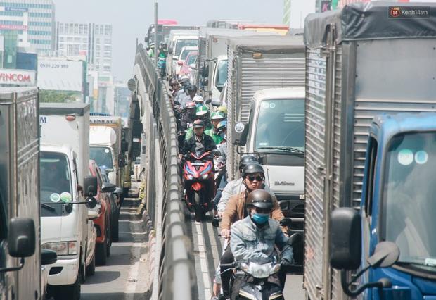 Chùm ảnh: Cửa ngõ sân bay Tân Sơn Nhất liên tục kẹt xe bất thường, ô tô dàn 2 hàng ép xe máy trên cầu vượt - Ảnh 2.