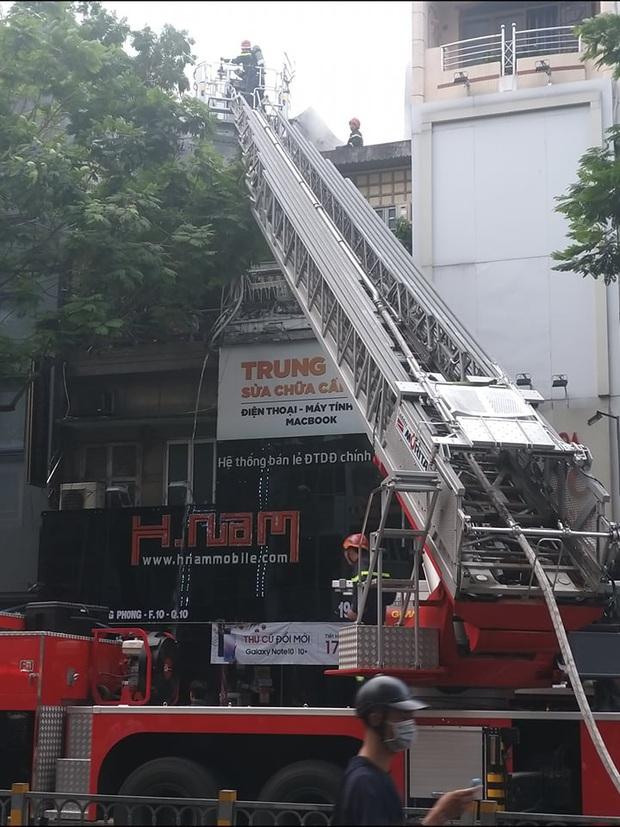 TP. HCM: Cửa hàng điện thoại di động bốc cháy ngùn ngụt, Cảnh sát dùng xe thang leo mái nhà dập lửa  - Ảnh 2.