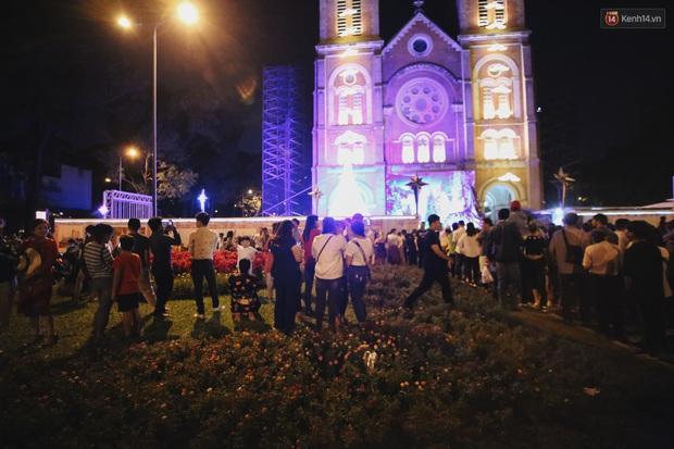 Bất chấp biển cấm, người dân vẫn giẫm đạp lên vườn hoa trước Nhà thờ Đức Bà trong đêm Noel ở Sài Gòn - Ảnh 1.