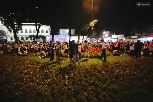 Bất chấp biển cấm, người dân vẫn giẫm đạp lên vườn hoa trước Nhà thờ Đức Bà trong đêm Noel ở Sài Gòn - Ảnh 7.