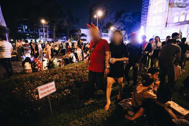 Bất chấp biển cấm, người dân vẫn giẫm đạp lên vườn hoa trước Nhà thờ Đức Bà trong đêm Noel ở Sài Gòn - Ảnh 2.