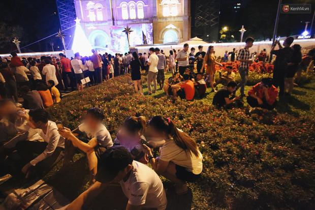 Bất chấp biển cấm, người dân vẫn giẫm đạp lên vườn hoa trước Nhà thờ Đức Bà trong đêm Noel ở Sài Gòn - Ảnh 4.
