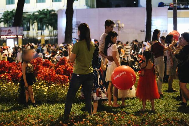 Bất chấp biển cấm, người dân vẫn giẫm đạp lên vườn hoa trước Nhà thờ Đức Bà trong đêm Noel ở Sài Gòn - Ảnh 10.