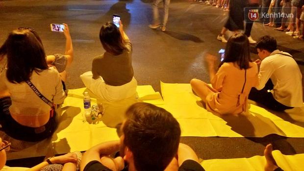 Hàng vạn người đổ về trung tâm chờ xem pháo hoa, các thánh tranh thủ ở Sài Gòn ăn nên làm ra nhờ bán giấy lót ngồi - Ảnh 4.
